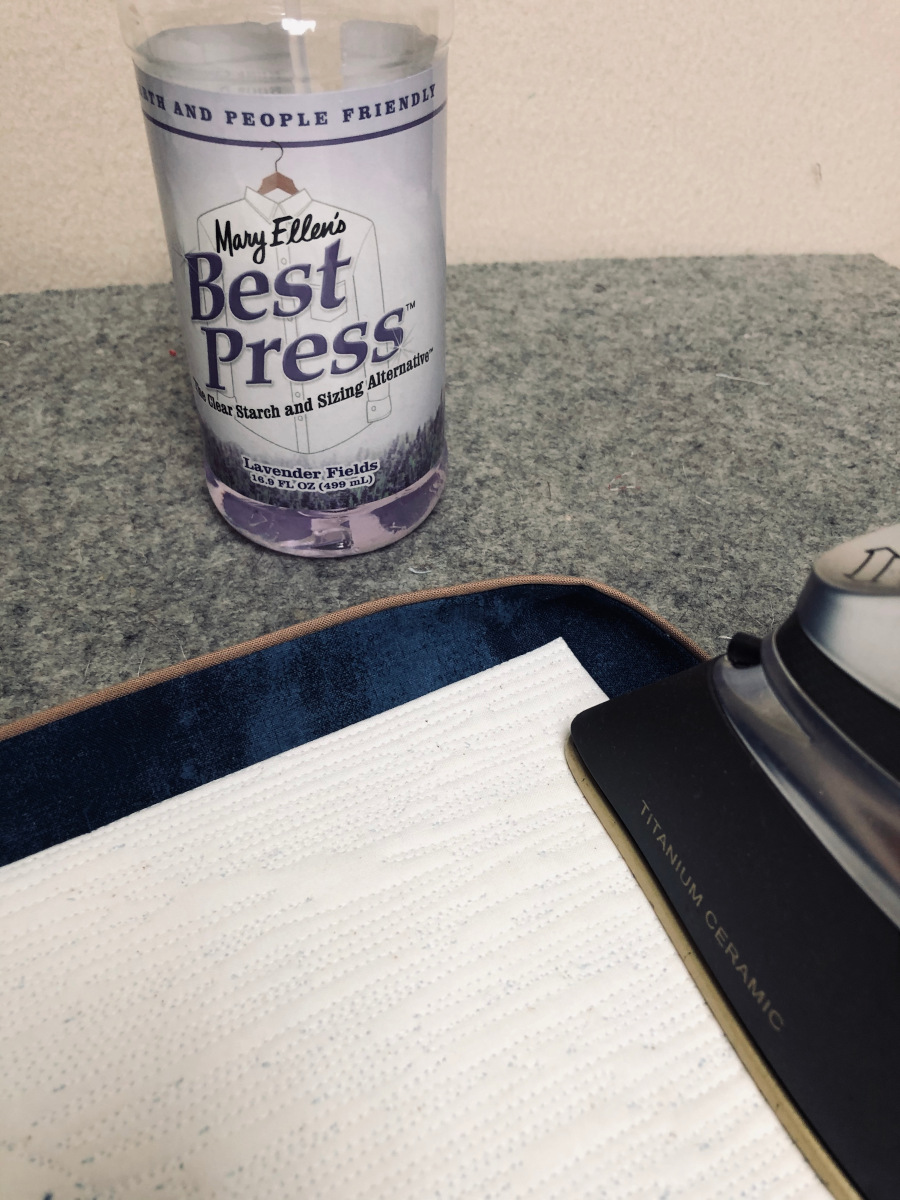Using an iron to press the binding away from the backing.