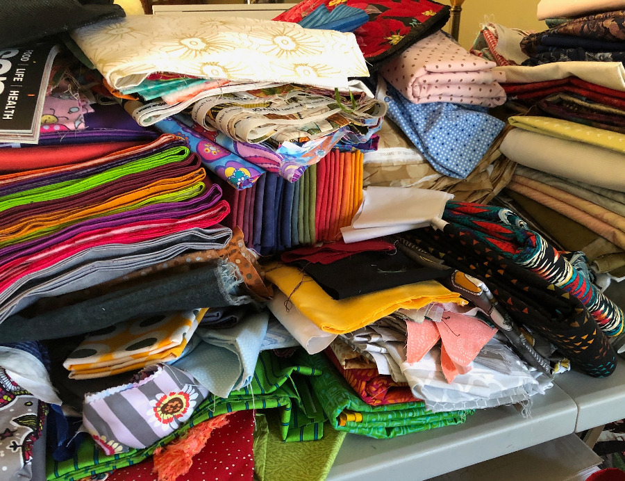 An unorganized fabric mess in a sewing room.